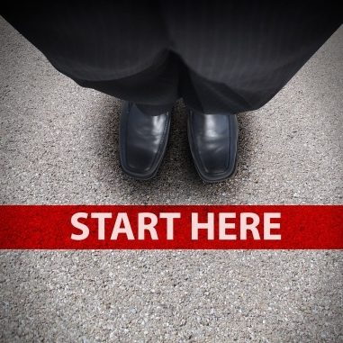 17352552 - a business man is looking down at his feet with a red race line that says start here to represent a journey